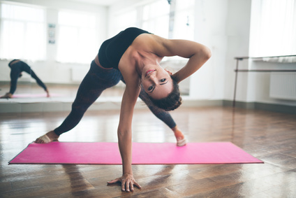 Young slim woman practicing pilates exercises